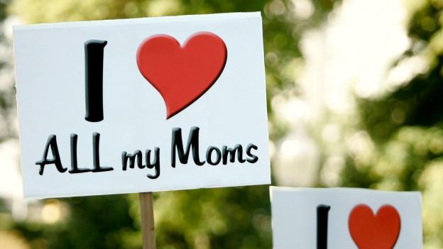 Zwei Pappschilder, auf denen steht: I Love all my Moms.