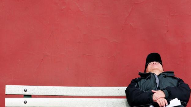 Mann schläft sitztend auf einer Bank.