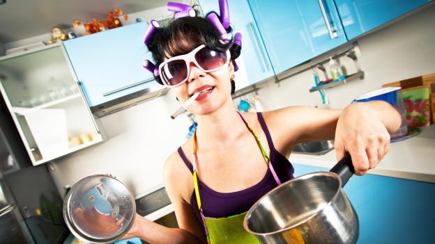Frau mit Sonnenbrille, Haarwicklern und Joint im Mund steht in einer knallbunten Küche.