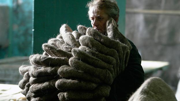 Ein Mann hält einen Stapel mit etwa 15 Paar Filzschuhen.