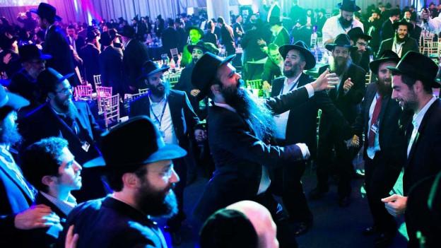 Jüdische Männer tanzen im Party-Licht.