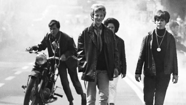 Schwarzweiss Foto einer Gruppe Jugendlicher, die auf der Strasse laufen. Einer schiebt ein Motorrad.