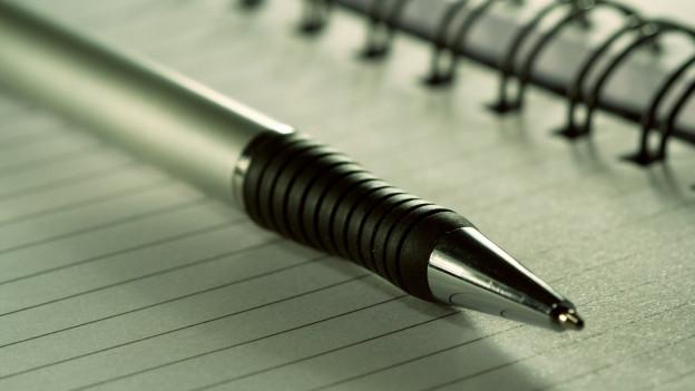 Ein Stift und ein Block.