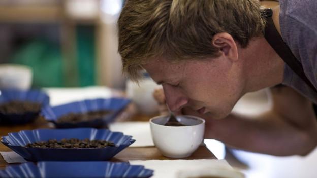 Ein Mann riecht an Kaffeebohnen.