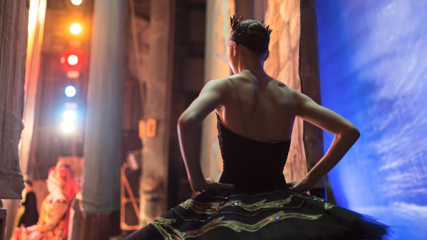 Eine Tänzerin wartet hinter dem Vorhang einer Theaterbühne auf ihren EInsatz