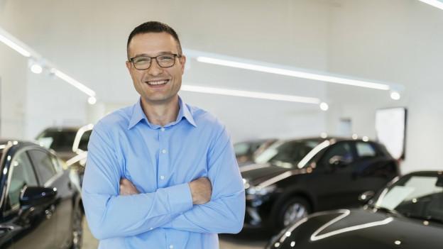Ein Autohändler lächelt in die Kamera.