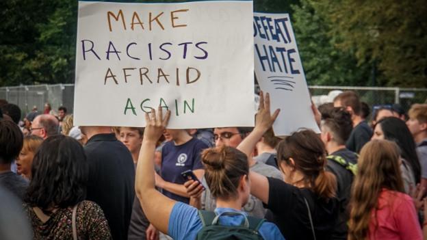 Demontrantin hält einen Karton mit der Aufschrift «Make racists afraid again»