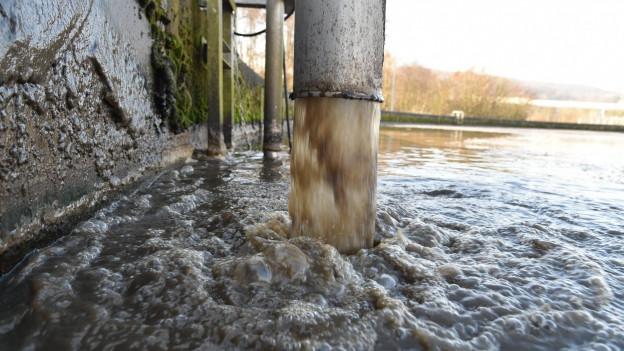 Abwasser stürzt aus einem Rohr in ein Klärbecken