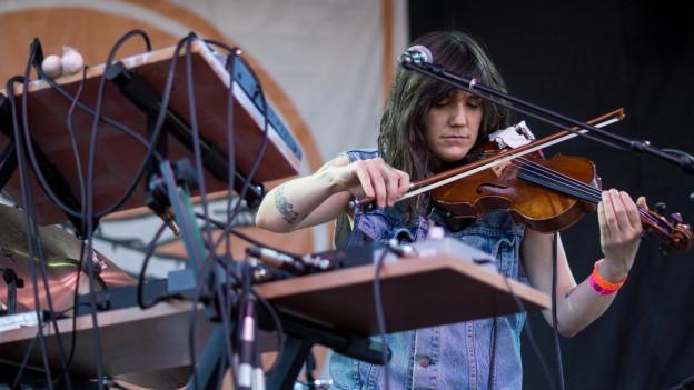 Die Loop-Performerin Emily Wells spielt Geige, im Vordergrund vielverkabelte Mischpulte