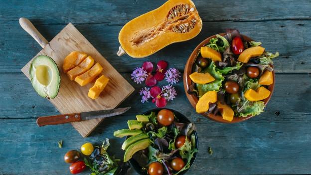 Bunte Salate und Gemüse auf einem Holztisch
