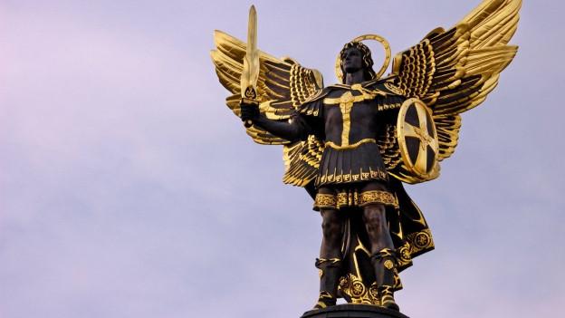 Eine überlebensgrosse Statue eines Engels mit Schwert und Schild bewaffnet