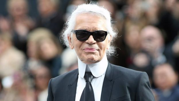 Ein extravagant gekleideter Herr mit langen weissen Haaren, schwarzer Sonnenbrille und weissem Stehkragen, der ihm bis zum Kinn reicht