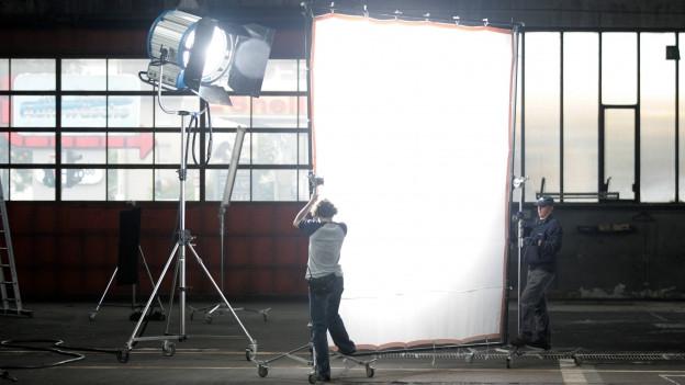 In einer leeren Fabrikhalle ist ein grosser Scheinwerfer auf eine weisse Leinwand gerichtet