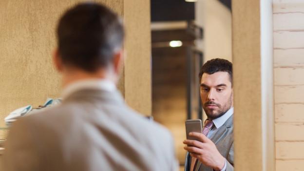 Ein Mann macht ein Selfie vor einem Spiegel