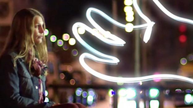 Eine junge Frau sitzt in der Dunkelheit, eine überdimensionale Leuchthand nähert sich ihr