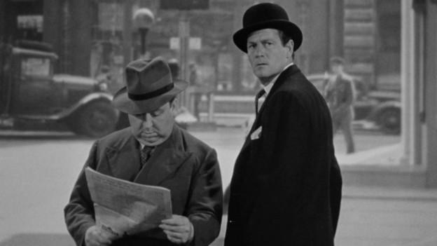 Zwei Männer in Mänteln und Hüten, der linke liest eine Zeitung