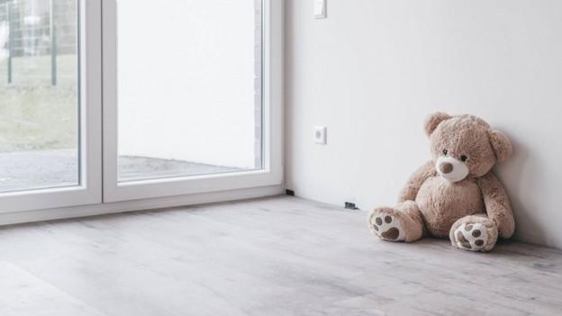 Ein Teddy sitzt am Boden in einer Wohnung.