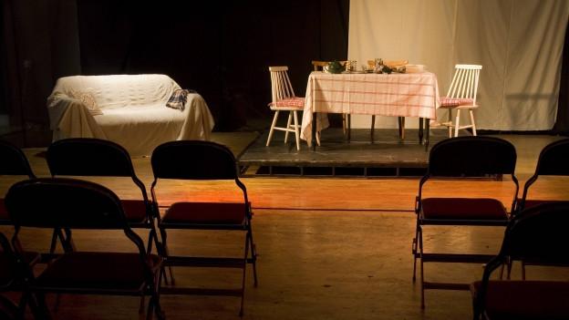 Publikumsstühle vor einer Theaterbühne