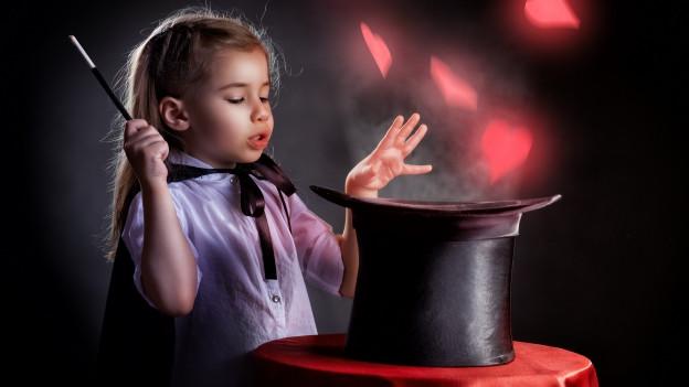 Kleines Mädchen zaubert etwas aus ihrem Hut