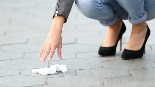 Eine Frau hebt Müll vom Boden auf
