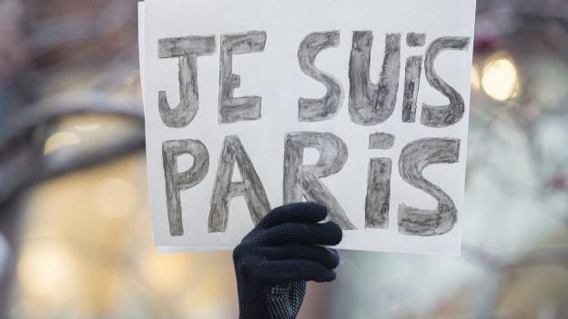 """Hand hält Schild mit der Aufschrift """"Je suis Paris"""""""