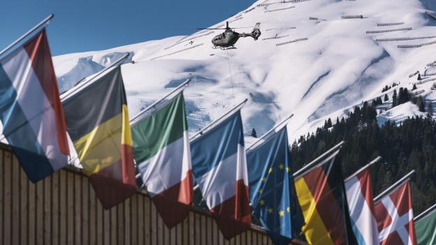 Flaggen mehrerer Länder hängen an einem Absperrzaun, oben kreist ein Helikopter