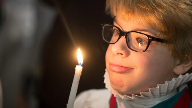 Ein Junge in der Kirche schaut eine leuchtende Kerze an.