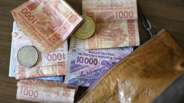 Ein Portemonnaie mit CFA Francs der Ostafrikanischen Zentralbank.
