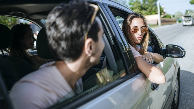 Im Auto schauen sich eine Beifahrerin und ein junger Mann auf dem Rücksitz durch die geöffneten Autofenster an