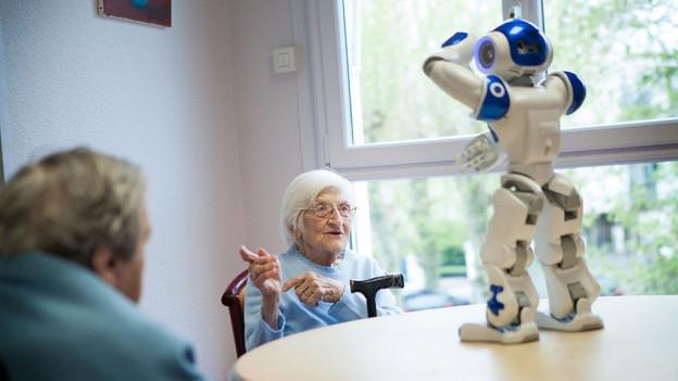 Ein Roboter steht auf einem Tisch. Ältere Menschen machen seine Bewegungen nach.