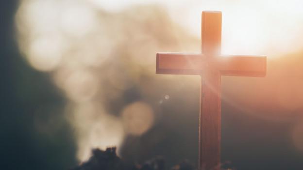 Ein Holzkreuz in einer nebligen Morgendämmerung