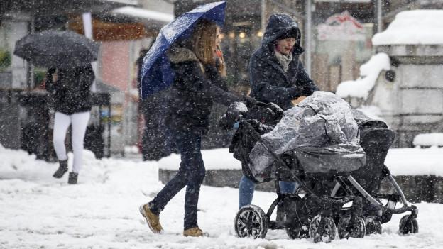 Zwei Frauen schieben einen Kinderwagen durch eine verschneite Stadt