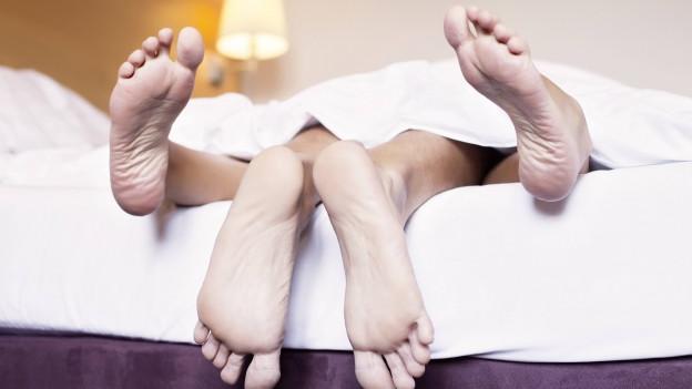 Unter einer Bettdecke liegen aufeinander zwei Personen, von denen man nur die Füsse sieht