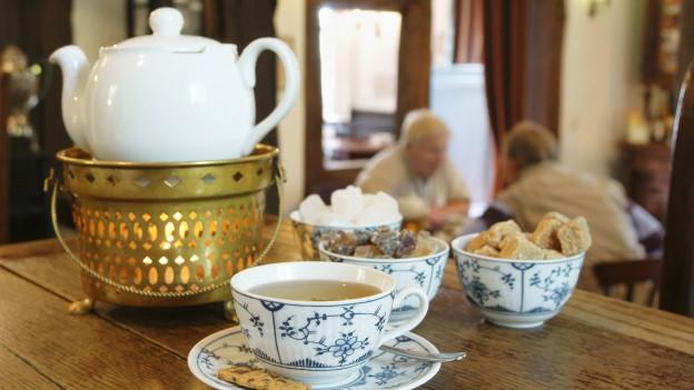 Teekanne mit Tassen in einem Restaurant.