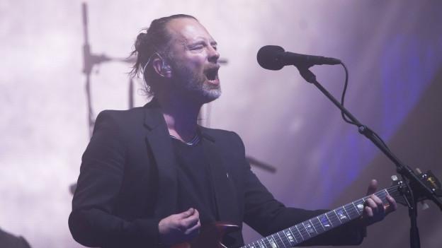 Mann mit E-Gitarre singt in ein Mikrofon