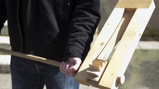 Mann hält mit beiden Händen ein grosses hölzernes Instrument an einem Stock