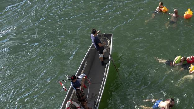 Menschen kühlen sich im Rhein ab.