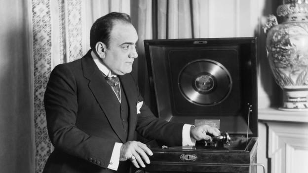 Schwarzweiss-Fotografie: Ein Sänger steht neben einem Phonograph..