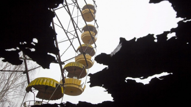 Ein altes Riesenrad, gesehen durch ein Trümmerloch.