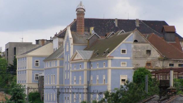 Die Fassade des Hauses ist bunt angemalt, dahinter offenbart sich graue Tristesse