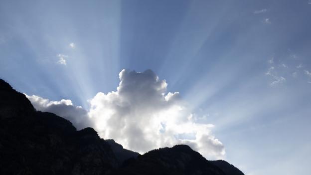 Ein blauer Himmel überfängt einen Berg. Eine Wolke steht zentral im Bild. Hinter ihr scheint die Sonne hervor.