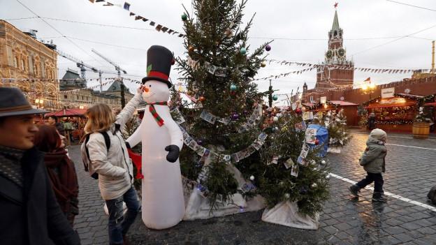 Menschen vor einem Weihnachtsbaum in Moskau.