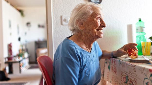 Eine ältere Frau ist ein Konfitüre-Brot.