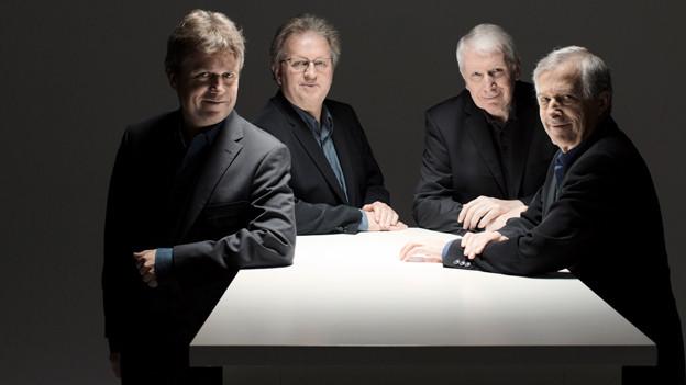Vier Männer in Anzügen stehen an einem Tisch.