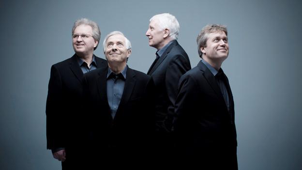 Vier Männer im Anzug stehen schauen nach oben.