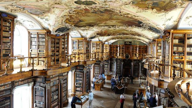 Blick auf einen barocken Saal. Die Wände sind voller Büchergestelle.