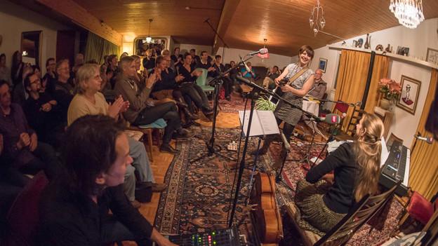 Eine Sängerin mit Gitarre vor einem kleinen Publikum.