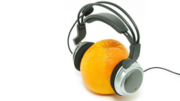 Eine Orange trägt einen Kopfhörer