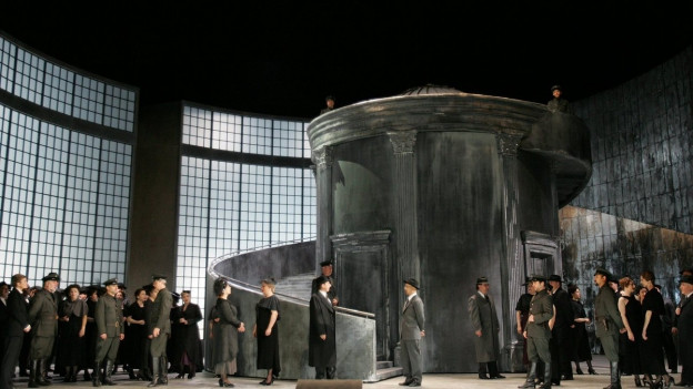 Bühnenbild einer Oper mit einem Wachturm in der Mitte. Am Boden sind mehrere Schauspieler in dunkler Abendgarderobe und uniformierte Männer im Bühnenraum verteilt.