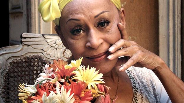 Ein Porträt von Omara Portuondo. Sie trägt ein gelbes Tuch um den Kopf geschlungen. Ein Blumenstrauss mit gelben, weissen und orangen Margriten steht vor ihr.